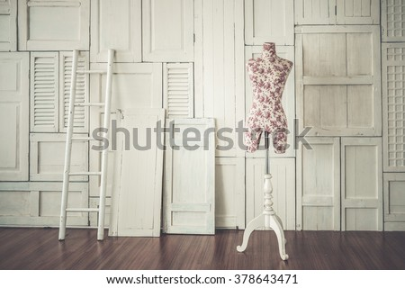 Vintage mannequin in cozy designer studio with ladder against the white wall and wooden laminate floor, art color filter applied