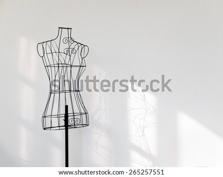 Vintage mannequin stand at white wall. - stock photo