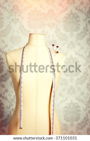 Vintage mannequin wearing a tape measure and with heart shaped pins - stock photo