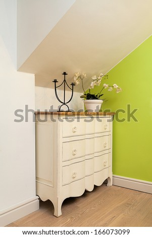 Vintage mansion - a cream chest of drawers with a flower and a candle holder - stock photo