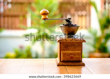 Vintage manual coffee grinder with coffee beans on wood table - stock photo