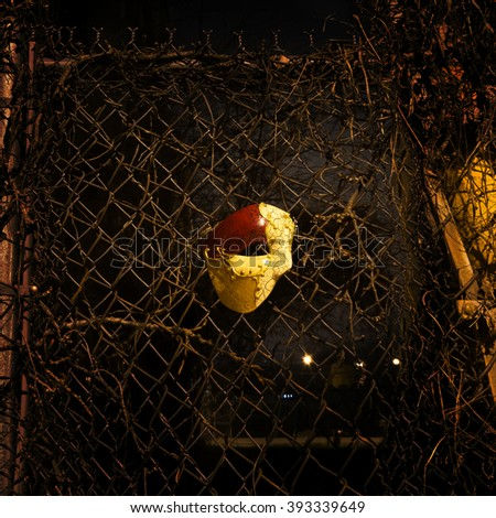 Vintage Mask on Rusty Steel Fence - stock photo