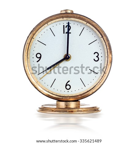Vintage mechanical alarm clock showing eight o'clock isolated over white - stock photo