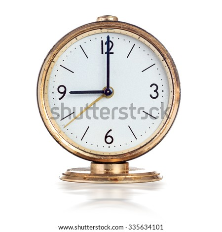 Vintage mechanical alarm clock showing nine o'clock isolated over white - stock photo