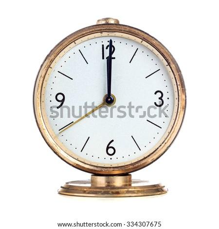 Vintage mechanical alarm clock showing twelve o'clock isolated over white - stock photo
