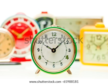 Vintage mechanical wind-up alarm clocks on white background, shallow focus - stock photo