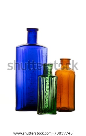 """Vintage medicine bottles; blue, green and brown poison bottles, isolated on white ground; moulded into the glass is the legend, """"Not to be taken"""" - stock photo"""
