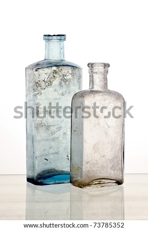 Vintage medicine bottles; two colourless poison bottle; reflections at base of image - stock photo