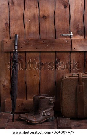 Vintage men's boots, suitcase and umbrella. Men's things near the wooden fence. - stock photo