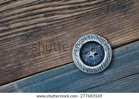 vintage metal Button for clothes on an old wooden surface of board