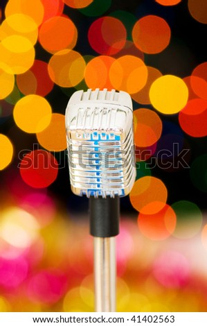 Vintage microphone against blurred lights - stock photo