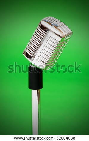 Vintage microphone against the bright green background - stock photo