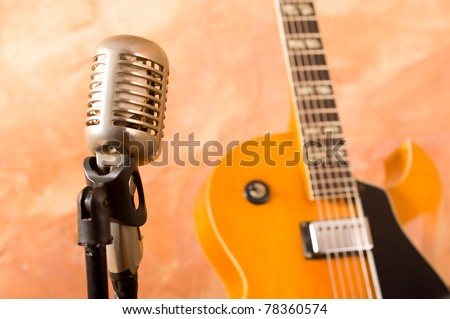 Vintage microphone and classic guitar waiting on stage - stock photo