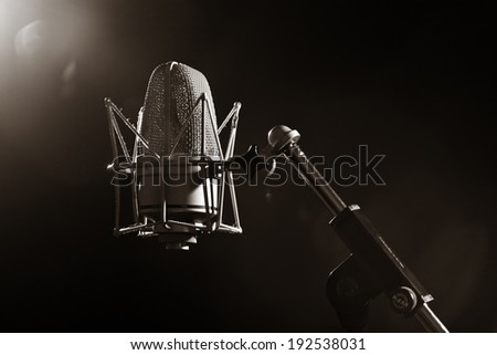 Vintage microphone closeup isolated on a dark background - stock photo
