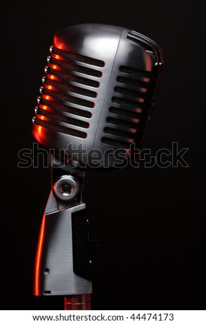 Vintage microphone on black with red highlights - stock photo