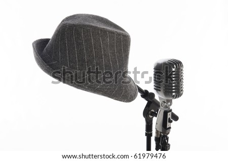 Vintage microphone on stand beside gray men's hat on second stand - stock photo