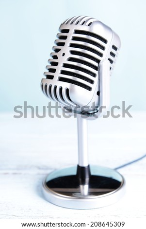 Vintage microphone on table on light blue background