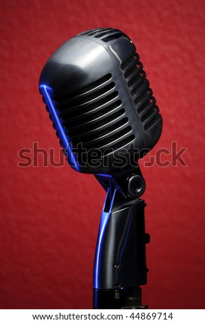 Vintage microphone with blue highlights on red background - stock photo