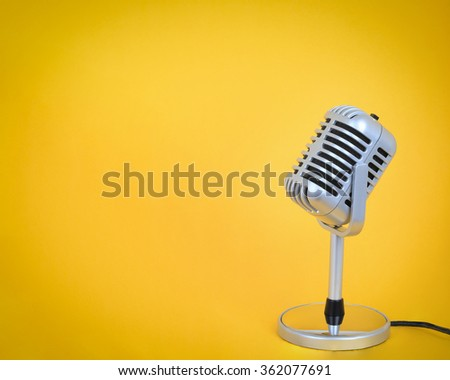 Vintage microphone with  yellow background. - stock photo