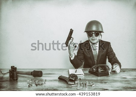 Vintage military businessman sitting at office desk with hand gun - stock photo
