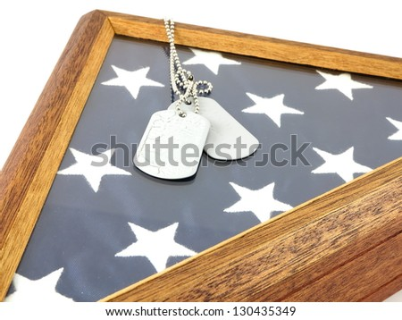 Vintage military dog tags on wooden flag display case and American Flag - stock photo