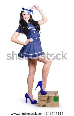 Vintage military photo of a beautiful navy woman in sailor outfit and hat standing on a resupply ammo box. Retro Pinups - stock photo