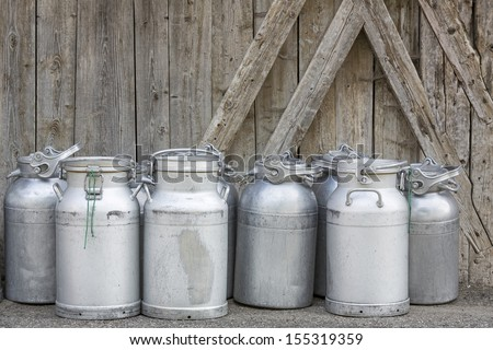 Vintage milk cans in rural Northern Italy - stock photo