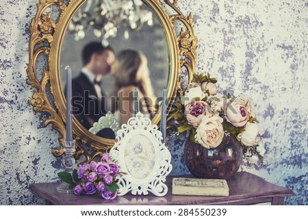 Vintage mirror with the bride and groom in the reflection on the wedding day - stock photo