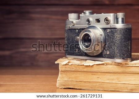 Vintage 35mm film camera on old book over wooden defocused background - stock photo