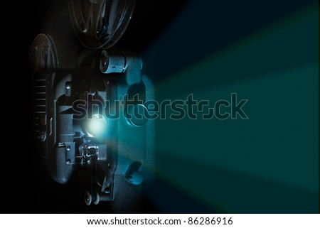 Vintage 8 mm film projector in dark room with reels and light beam - stock photo