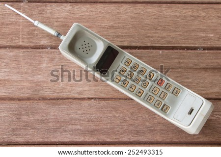 vintage mobile phone on brown wood  background. - stock photo