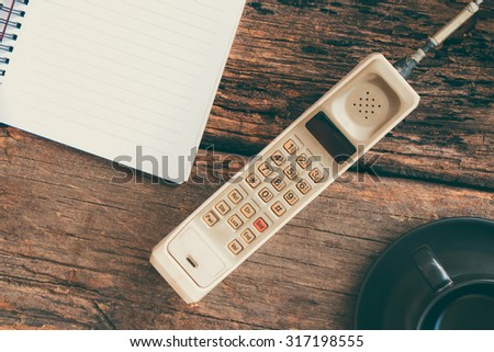 vintage mobile phone with blank paper note and cup of coffee (vintage style) - stock photo