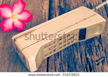 vintage mobile phone with flower(vintage style) - stock photo