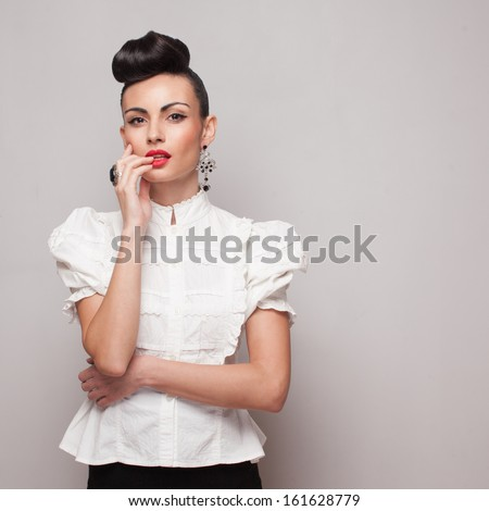 Vintage model posing in white shirt on grey background - stock photo
