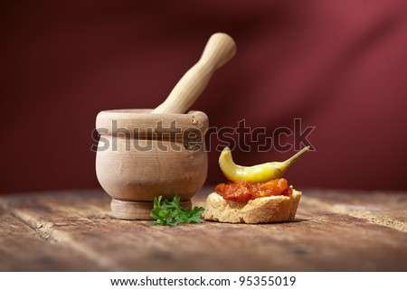 Vintage mortar and  bread with hot pepper sauce on old wooden table and red background