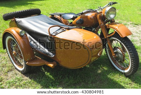 vintage motorcycle with sidecar parked on green grass - stock photo