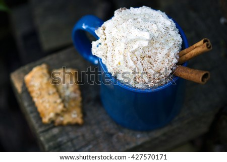 Vintage mug of cocoa with cinnamon sticks decorated with whipped cream. Rustic style. - stock photo