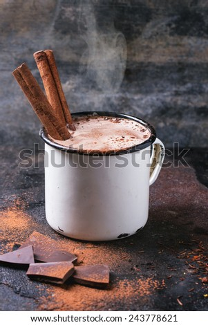Vintage mug of hot chocolate with cinnamon sticks over dark background - stock photo