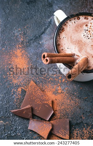 Vintage mug of hot chocolate with cinnamon sticks over dark background. Top view. - stock photo