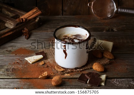Vintage mug with hot chocolate served with chunks of white and dark chocolate and almonds on old wooden table - stock photo