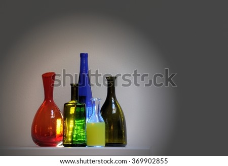 Vintage multicolor group of bottles in a row on gray background - stock photo