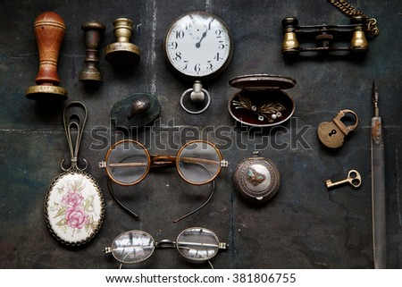Vintage museum binoculars, glasses, stamps, pocket watch, small lock with key - stock photo