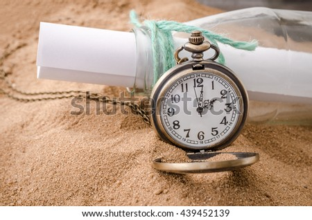 Vintage necklace watch on sand beach with message bottle - stock photo