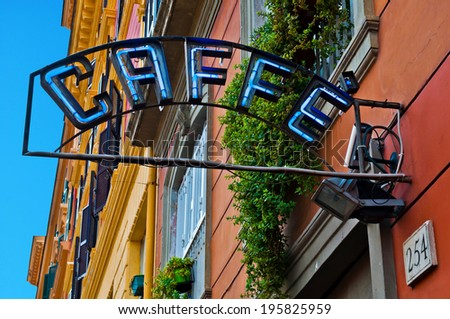 vintage neon caffe (coffee) sign hanging against colorful buildings in Rome, Italy