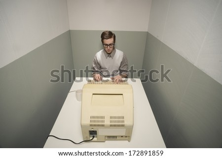 Vintage nerd guy working on old computer in a small room. - stock photo