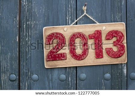 Vintage New Year date sign board on wooden planks background with rope hanging on nail - stock photo