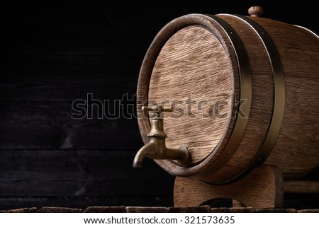 Vintage oak barrel on rack on old wooden table still life with copy space - stock photo