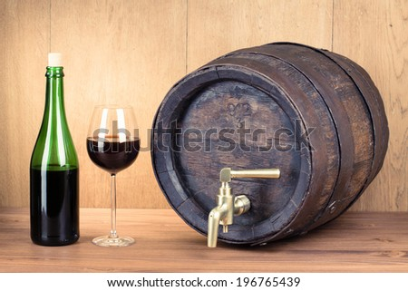 Vintage oak wood barrel, bottle and glass of red wine - stock photo