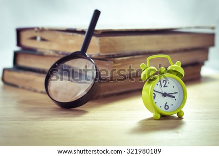Vintage of green alarm clock,magnifying glass  and stack of books on a white background,selective focus - stock photo