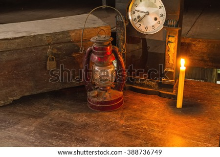 Vintage oil lamp ,old wooden box ,alarm clock and candlelight on old wooden touch-up in still life concept ,dark tone - stock photo